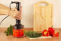 Hands chefs mixed red pepper and tomato in blender Royalty Free Stock Photography