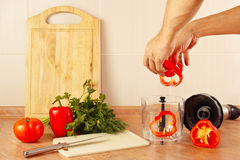Hands chefs put chopped red pepper in blender Stock Photo