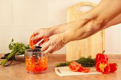 Hands chefs put chopped tomato in blender Stock Images