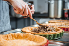 Hands of cheif cook cooking and putting filling into pie Stock Photography
