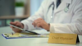 Hands of chief physician checking medical reports on tablet PC, application. Stock footage stock video