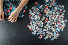 Hands of a child doing a puzzle. At table Stock Images