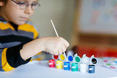 Hands of child drawing with colorful watercolors royalty free stock image