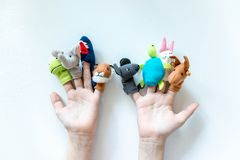 Hands of a child with finger puppets, toys, dolls close up on white background - playing puppet theatre and children entertainment. Concept royalty free stock photo