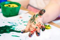 Hands of child girl boy dirty in childrens finger paint studying drawing art. Fingers holding tassel Concept idea of children& x27;s education preschool Royalty Free Stock Photos