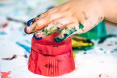 Hands of child girl boy dirty in childrens finger paint studying drawing art. Fingers holding tassel Concept idea of children& x27;s education preschool royalty free stock photography