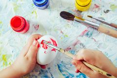 Hands of the child hold a brush with red paint and paint egg by Easter, a close up. The top view stock photography