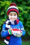 Hands of child holding big cup with snowflakes and hot chocolate Royalty Free Stock Photos