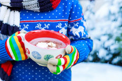 Hands of child holding big cup with snowflakes and hot cocoa and Stock Image