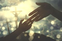 Hands of child holding father`s hand. With three crucifixes in the background stock photography