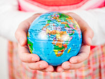 Hands of a child holding globe Stock Photo