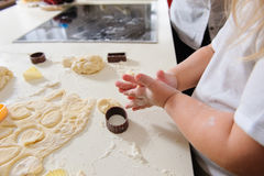 Hands of  child knead dough. Children's hands knead the dough for baking cookies, dough, flour, baking tins on a white table in the background Royalty Free Stock Image