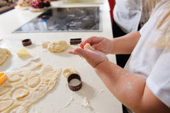 Hands of  child knead dough. Children's hands knead the dough for baking cookies, dough, flour, baking tins on a white table in the background Royalty Free Stock Photos