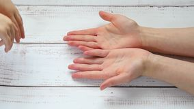 Hands of a child in the mother`s hands close-up, hand in hand against the background of a wooden table, in slow motion