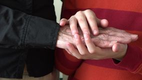Hands of child petting his grandmother old wrinkled hands stock video