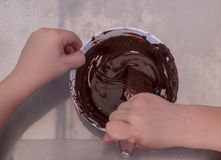 Hands of a child play the pastry chef mixing chocolate in a bowl Stock Photography