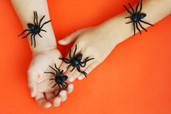 Hands of a child playing with black rubber spiders toys on orange paper background. Halloween october concept. stock photography