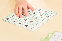 Child holds card with numbers board game royalty free stock images