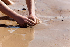 Hands of the child playing in sand at water Stock Image