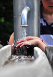 Hands of child playing with water in street water pump Royalty Free Stock Image