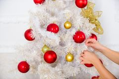 Hands of child put christmas ornament ball on artificial white tree. Christmas decoration concept. Eco movement and royalty free stock images