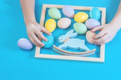 Pastel scattered Easter eggs with kids hands royalty free stock photos