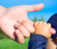 Hands of child son and father. Trust family hands of child son and father on field nature outdoor Royalty Free Stock Photo