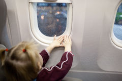 Hands of child in the window of airplane Stock Photo