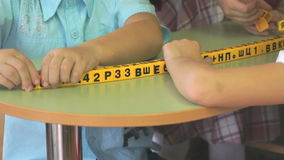 Hands of children studying numbers and letters. Hands of children touching special learning symbols and studying numbers and letters during school lesson stock video footage