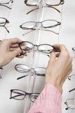 Hands Choosing Eyeglasses From Rack. Closeup of a woman's hands choosing eyeglasses from rack Stock Photos