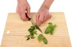 Hands chopping basil Stock Image