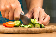 Hands chopping cucumber for salad Royalty Free Stock Photos