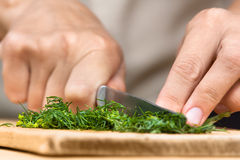 Hands chopping fresh dill on the cutting board Stock Photo
