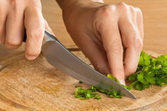 Hands chopping parsley leaves on the cutting board, closeup Stock Photo
