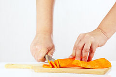 Hands chops carrot on a cutting board. Close up Stock Photos