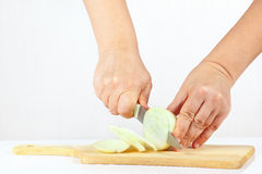 Hands chops raw onion on a cutting board. Close up Stock Photography