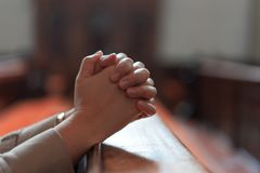 A Christian girl is sitting and praying with broken heart in the. Hands of a Christian girl is sitting and praying with humble heart in the church stock images