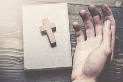 Cross, book and man hand. Hands of Christian man praying on wooden desk Royalty Free Stock Photography