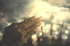 Hands of a Christian man with rosary. Hands of a Christian man holding a rosary while praying to god with three crucifixes under sunbeam in the hill stock photography