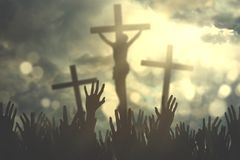 Hands of Christian people with crucifixes. Hands of Christian people praising and praying under three crucifixes at sunrise royalty free stock images