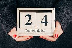 Hands with Christmas Eve date. Woman`s hands holding calendar with Christmas Eve date Stock Image