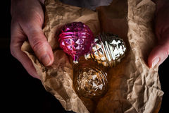 Hands with Christmas tree decorations in wrapping paper Stock Images