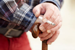 Hands with cigarette on cane Royalty Free Stock Photos