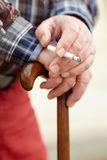 Hands with cigarette on cane Royalty Free Stock Images