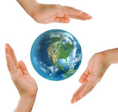 Hands in circle sheltering globe Stock Photo