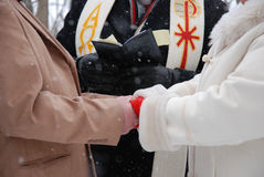 Hands clasped at outdoor winter wedding ceremony. The bride and groom holding hands during the ceremony at an outdoor winter wedding ceremony Stock Photos