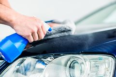 Hands cleaning car with spray cleaner and microfiber towel. Close-up of male hands cleaning car with spray cleaner and microfiber towel outdoors at car wash Royalty Free Stock Photos