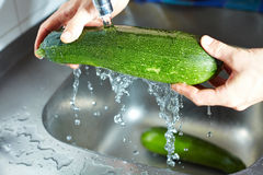 Hands cleaning courgette Stock Photo