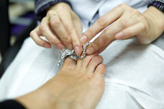 Hands, cleaning finger nails of women's foot Stock Images