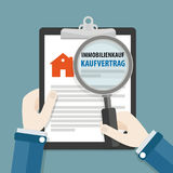 Hands Clipboard Loupe Immobilienkauf Kaufvertrag. German text Immobilienkauf Kaufvertrag, translate Real Estate Purchase Contract Stock Photos